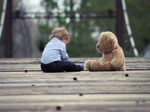 boy with a teddy bear sitting on the ground