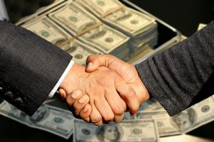 Handshake over a pile of money