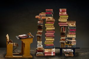 books stacked in front of the desk