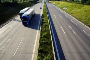 Two transport trucks on the highway.