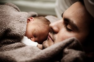Baby and father sleeping.