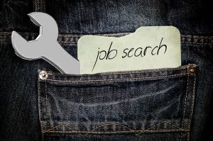 """Pants pocket with a tool and """"job searching"""" note."""