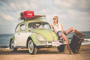 Girl with a car on the beach