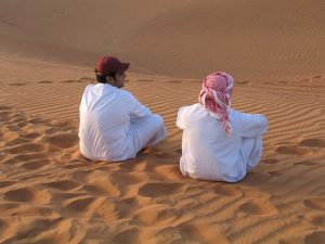 Two men sitting in a desert.