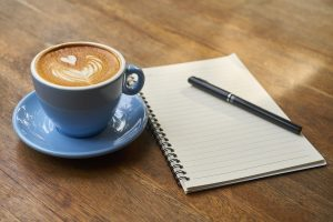 A cup of coffee next to a notebook.