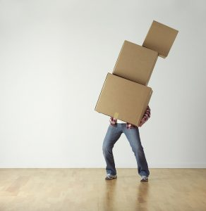 A man is carrying three moving boxes alone.