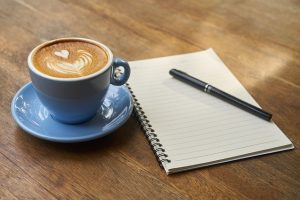 A notepad and a cup of coffee