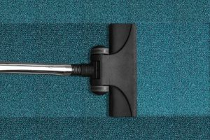Cleaning a carpet with a vacuum.