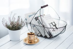 Plant, books and a cup on a coffee table.