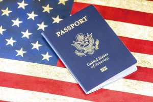 a blue USA passport on a USA flag - you will need it when finding a job in Kuwait