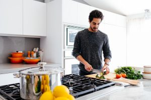 a man standing in the kitchen chopping vegetables