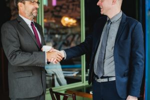 Two men in suits shaking hands in front of a cafe. When you're meeting new neighbours after the move, introduce yourself first.
