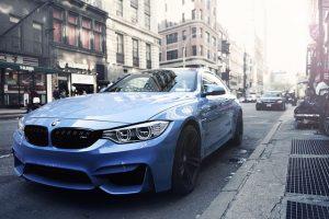 A blue BMW parked on a street