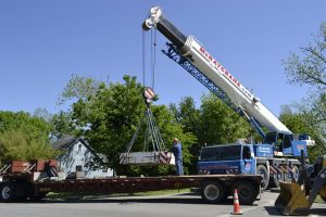 Crane is lifting machinery on the flatbed truck