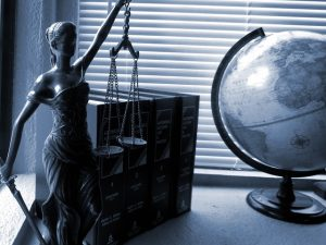A statue and a globe depicting laws about prohibited items for international shipping