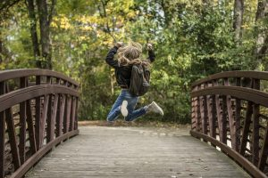 Happy girl jumping - How to help your kids settle into a new home after moving