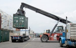 A crane lifting a container on a truck