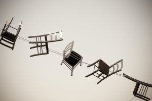 Five brown wooden chairs hanging from an electric cable