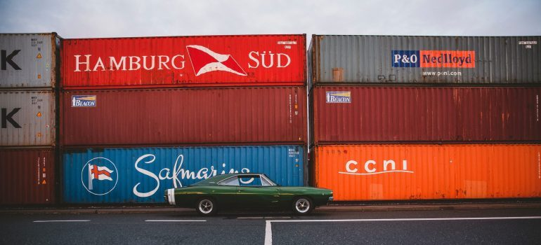 a classic car with containers in the background