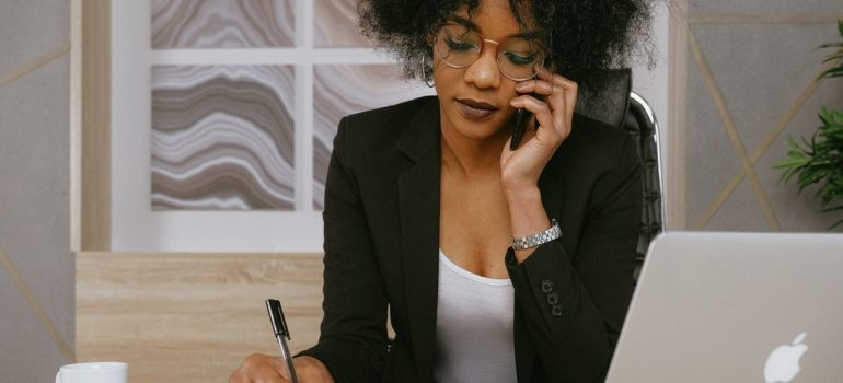 a woman talking on the phone while writing things down