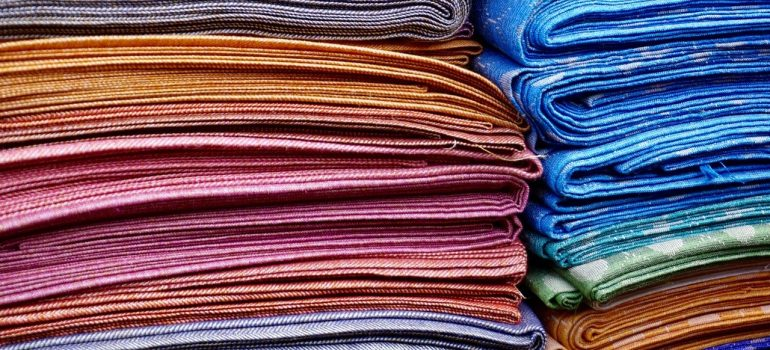 colorful clothes stacked on eachother as one of ways of importing textiles to the US