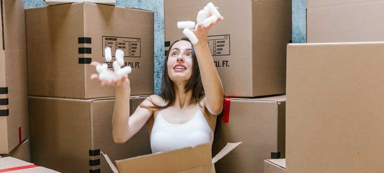 a woman playing with packing materials